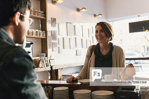 Kellner  der einer Kundin im Café Kaffee serviert