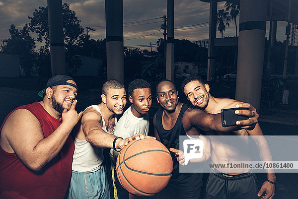 Men holding basketball using smartphone to take selfie