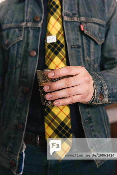 Cropped shot of young man wearing yellow tartan tie holding coffee shot glass