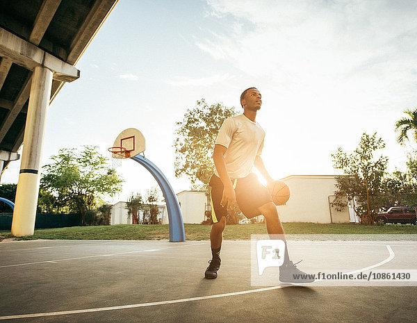 Men on basketball court holding basketball looking away