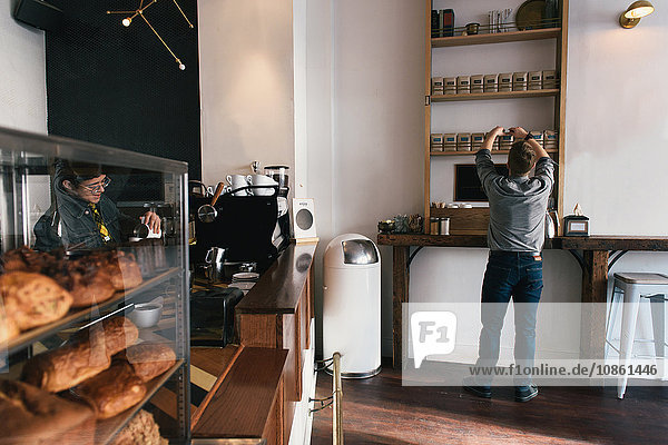Rear view of waiter removing coffee bean packet from coffee shop shelf