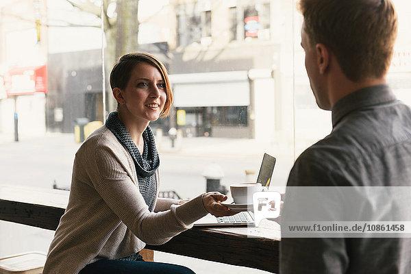 Kellner  der einer Kundin  die im Schaufenster eines Kaffeehauses sitzt  Kaffee reicht