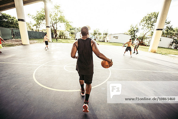 Full length rear view of young man walking on basketball court holding basketball