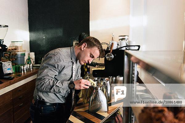 Junger männlicher Kellner  der an der Küchentheke eines Cafés arbeitet
