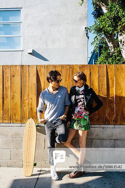 Junges Paar steht zusammen im Freien  Skateboard neben Mann an Wand gelehnt
