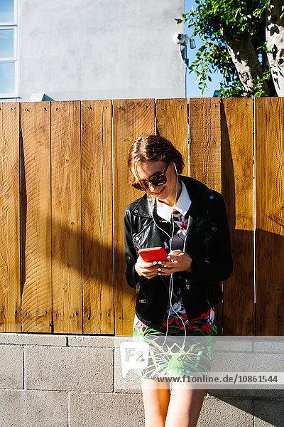 Junge Frau im Freien  mit Smartphone  mit Kopfhörern