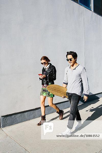 Junges Paar geht gemeinsam im Freien spazieren,  Frau benutzt Smartphone,  Mann trägt Skateboard