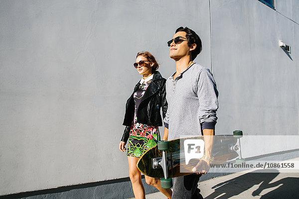 Junges Paar geht gemeinsam im Freien spazieren  Mann trägt Skateboard