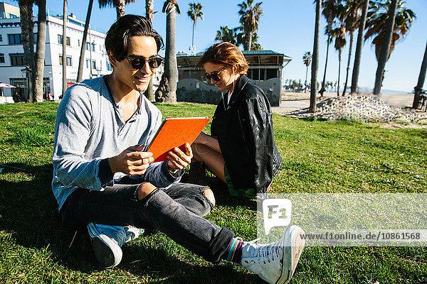 Junges Paar sitzt im Gras am Strand  Frau trägt Kopfhörer  Mann schaut auf digitales Tablet