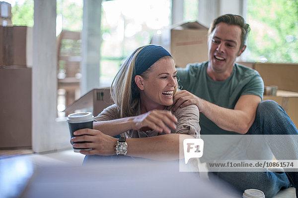 Umzug: Ehepaar macht eine Pause  sitzt in einem mit Pappkartons gefüllten Raum