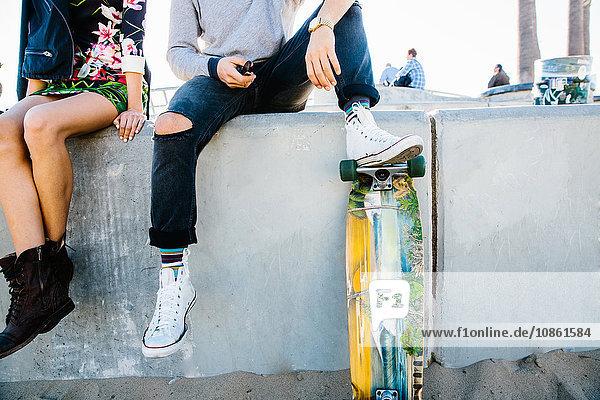 Junges Paar sitzt an der Wand  Mann ruht mit dem Fuß auf dem Skateboard  niedriger Abschnitt