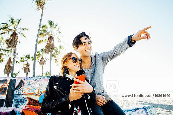 Junges Paar sitzt an der Wand  teilt sich Kopfhörer und schaut in die Ferne