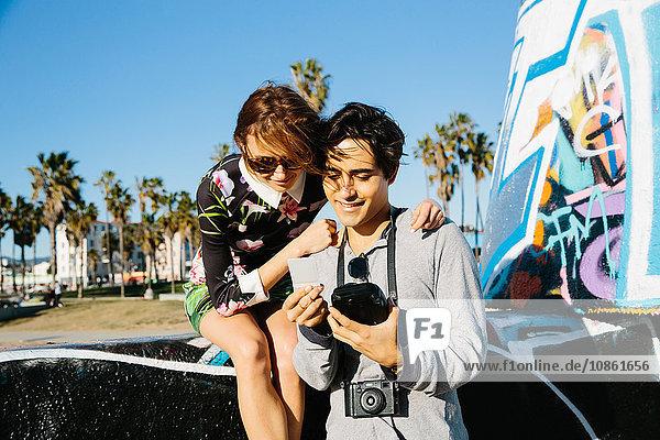 Junges Paar im Freien beim Betrachten eines Sofortbildfotos
