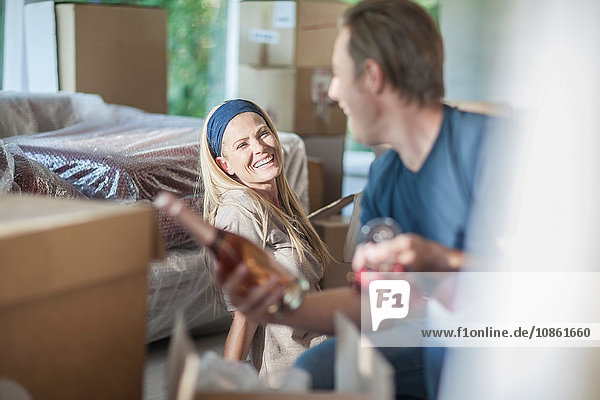 Moving house: couple in room with cardboard boxes  man holding bottle of champagne and champagne flutes