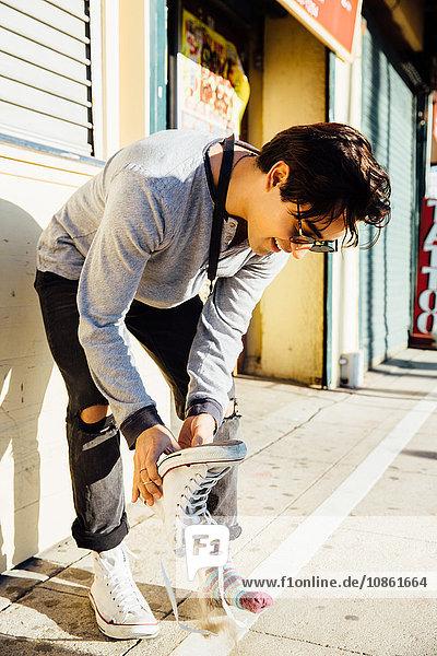 Junger Mann steht im Freien und leert Sand aus Schuhen