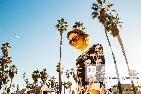 Junge Frau  die draußen spazieren geht  in der Nähe von Palmen  niedriger Blickwinkel