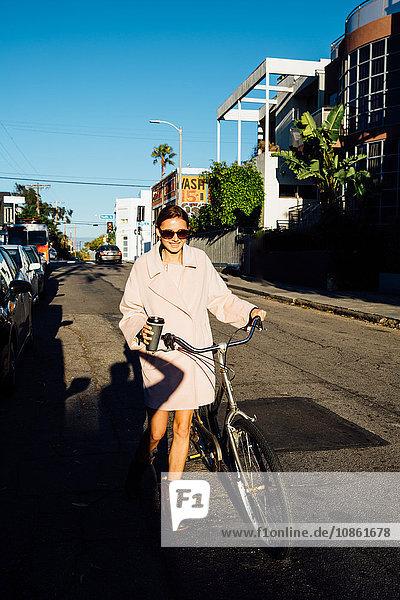 Junge stilvolle Frau schiebt Fahrrad die Straße entlang   Venice Beach  Kalifornien  USA