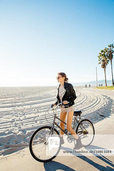 Junge Frau auf dem Fahrrad beim Blick vom Strand  Venice Beach  Kalifornien  USA
