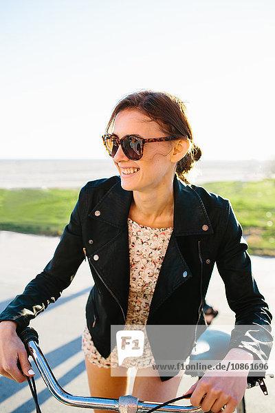 Junge Frau lehnt an der Küste am Fahrradlenker  Venice Beach  Kalifornien  USA