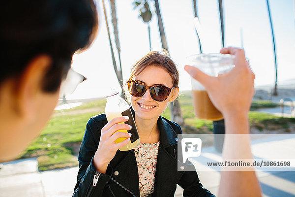 Über-Schulter-Ansicht eines jungen Paares  das einen Saft- und Kaffee-Toast ausbringt  Venice Beach  Kalifornien  USA