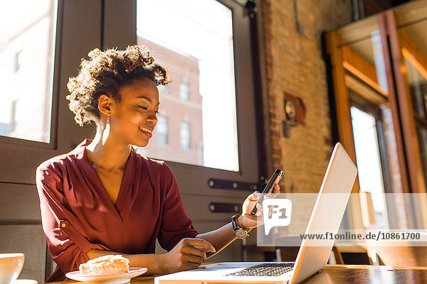 Young businesswoman sitting in cafe  using laptop and smartphone