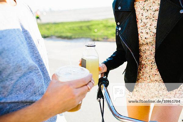 Schnappschuss eines jungen Paares mit Saft und Kaffeegetränken an der Küste