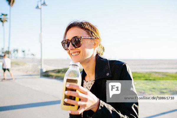 Junge Frau mit Fruchtsaft an der Küste  Venice Beach  Kalifornien  USA