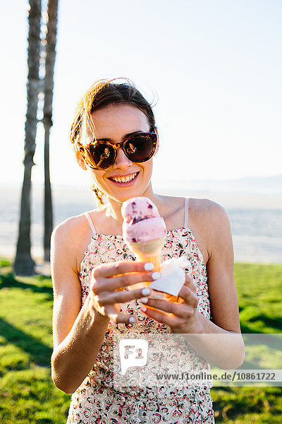 Porträt einer jungen Frau  die an der Küste Eiswaffeln isst  Venice Beach  Kalifornien  USA