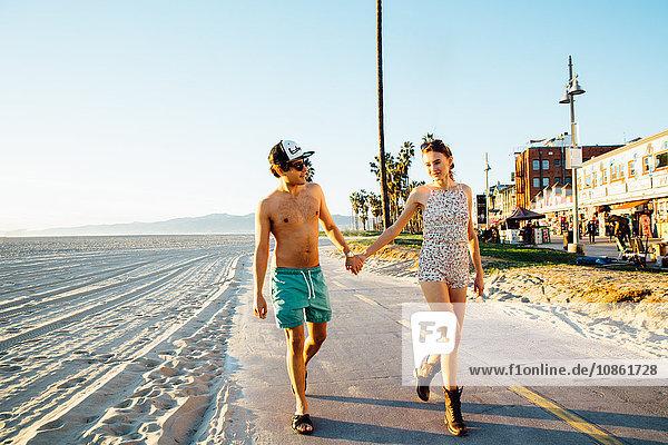Junges Paar im Badeanzug und in Shorts am Strand spazieren  Venice Beach  Kalifornien  USA