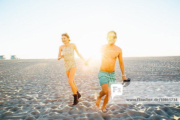 Junges Paar läuft in Badehose und Shorts am sonnenbeschienenen Strand  Venice Beach  Kalifornien  USA