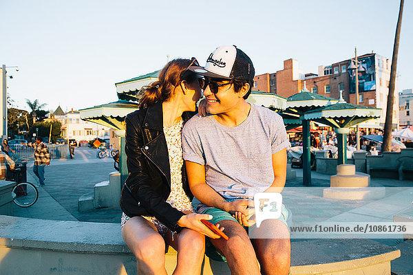 Romantisches junges Paar sitzt auf einer Mauer an der Küste  Venice Beach  Kalifornien  USA