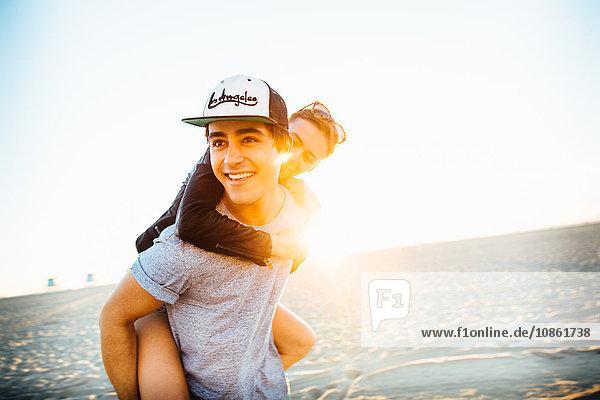 Junger Mann gibt seiner Freundin ein Huckepack am sonnigen Strand  Venice Beach  Kalifornien  USA