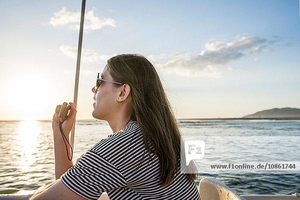 Junge Frau fotografiert Sonnenuntergang vom Mündungstourenboot aus  Tamarindo  Guancaste  Costa Rica