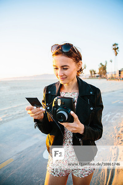 Young woman looking at instant photograph on beach  Venice Beach  California  USA