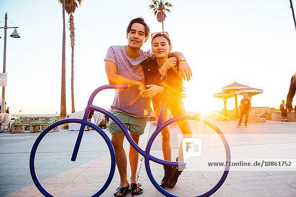 Porträt eines jungen Paares  das sich an eine Fahrradskulptur an der Küste lehnt  Venice Beach  Kalifornien  USA