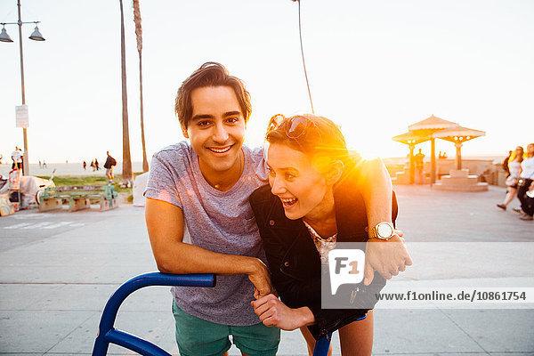 Porträt eines glücklichen jungen Paares  das sich an eine Fahrradskulptur an der Küste lehnt  Venice Beach  Kalifornien  USA