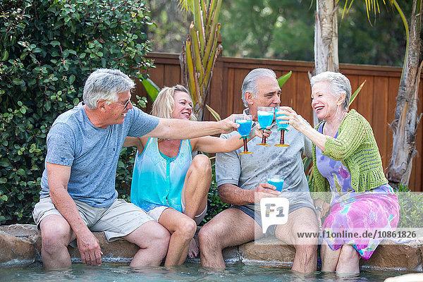Gruppe von Senioren stößt am Pool an