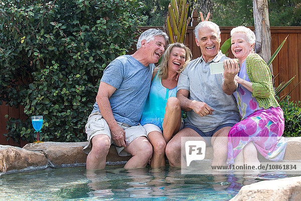 Group of seniors laughing at photos in smartphone at pool