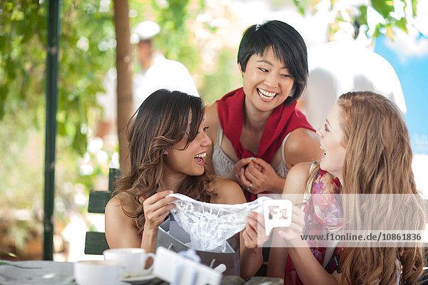 Drei Einkaufsfreundinnen lachen über neue Schlüpfer im Straßencafé in der Stadt