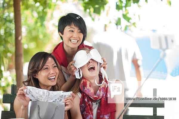Drei Einkaufsfreundinnen bedecken Augen mit BH im Straßencafé in der Stadt