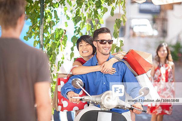 Romantisches junges Paar mit Einkaufstaschen auf dem Moped in der Stadt