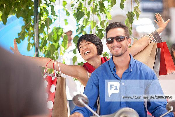 Glückliches junges Paar mit Einkaufstaschen auf dem Moped in der Stadt