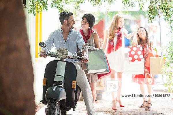 Junges Paar mit Einkaufstaschen auf Moped in der Stadt