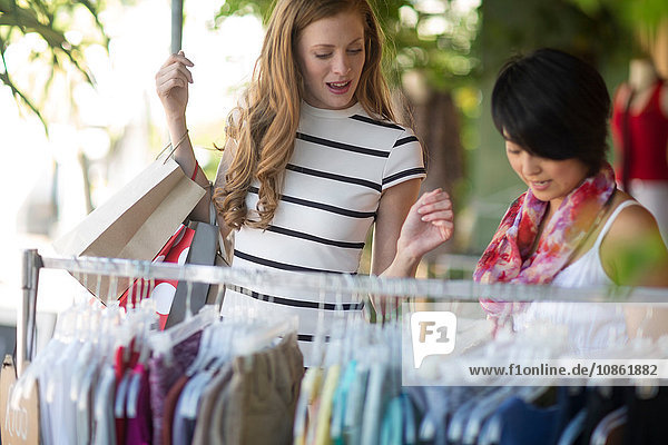 Zwei junge Frauen kaufen in der Stadt an der Kleiderstange ein