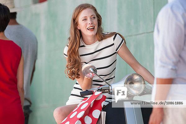 Junge Frau sitzt auf Moped in der Stadt