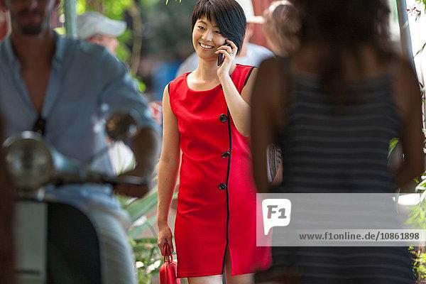 Junge Frau schlendert durch die belebte Straße der Stadt und unterhält sich mit ihrem Smartphone