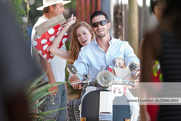 Paar mit Einkaufstaschen auf dem Moped