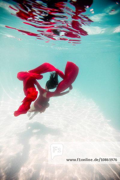 Frau in rotem Kleid  mit rotem Stoff drapiert  schwimmt unter Wasser
