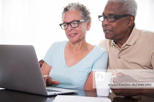 Älteres Ehepaar am Tisch sitzend  mit Laptop