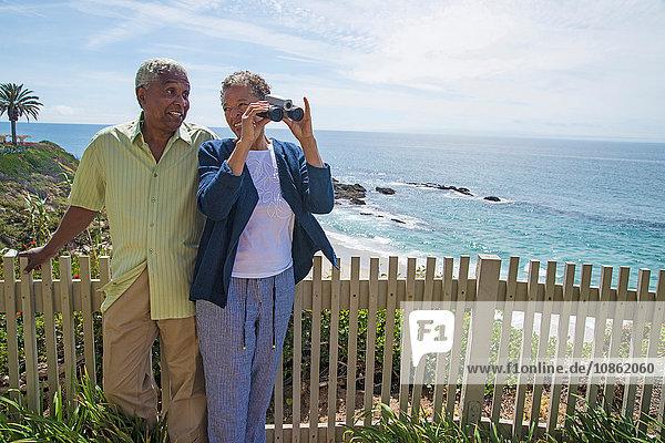 Älteres Paar im Freien  Frau schaut durch ein Fernglas  schaut auf die Aussicht